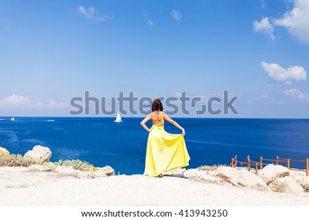 Young brunette woman in summer yellow dress standing on beach and looking to the sea.  - stock photo