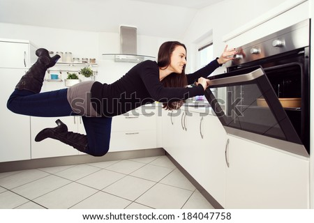 Young brunette woman in the kitchen levitating - stock photo