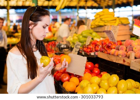 Young brunette woman is holding lemon and orange in her hands, near the boxes with peaches and tomatoes during shopping at fruit vegetable market, waist up