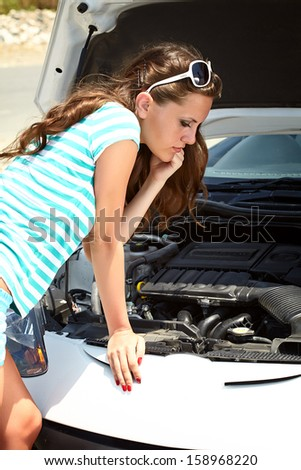 Young brunette woman is standing near broken car