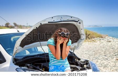 Young brunette woman is standing near broken car - stock photo