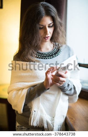 Young brunette woman is talking on mobile phone - stock photo