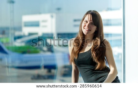 Young brunette woman is waiting to departure in the airport - stock photo