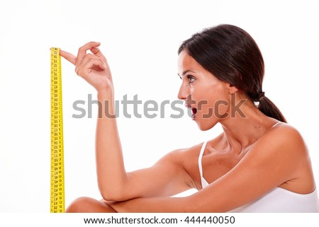 Young brunette woman looking at tape measure with her mouth open in surprise wearing a white tank top and her hair tied back, isolated