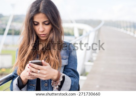 Young brunette woman looking her smart phone outdoors - stock photo