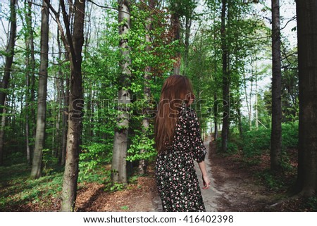 Young brunette woman lost in the green dark coniferous forest  - stock photo