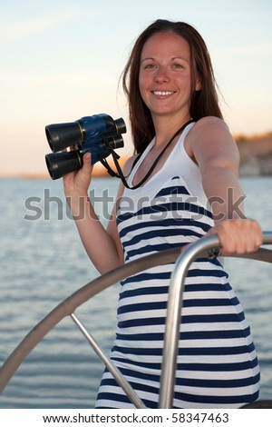 young brunette woman on the yacht with binocular