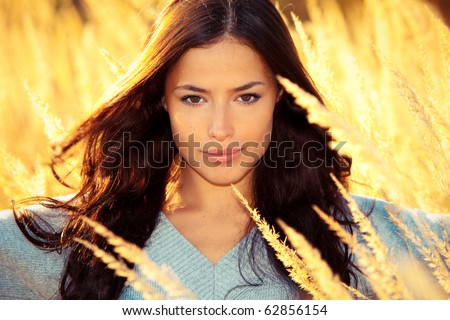 young brunette woman  portrait at sunny yellow autumn field