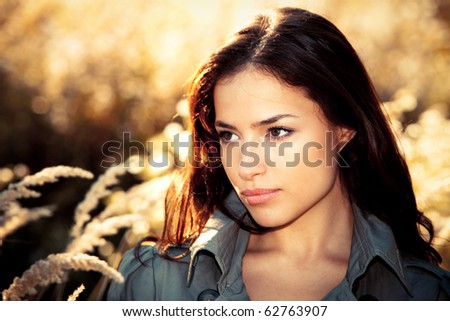 young brunette woman  portrait in autumn field - stock photo