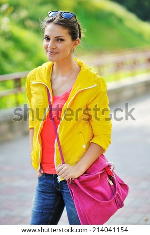 Young brunette woman portrait in colorful clothes in summer park - stock photo