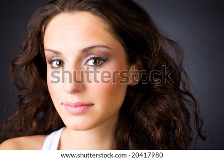 Young brunette woman portrait. On dark background.