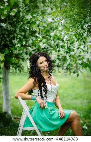 Young brunette woman portrait sitting on white chair in blooming apple tree park