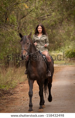 Young brunette woman riding a horse - stock photo