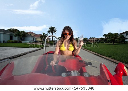 Young Brunette woman riding a Red Beach Car - stock photo