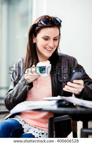 Young brunette woman sitting at a coffeeshop relaxing with her Cappuccino / Coffee while sitting outdoors
