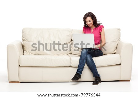 young brunette woman sitting comfortable with laptop on couch - stock photo