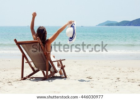 Young brunette woman sitting on the beach, looking at the sea. Summer photo. Vietnam.
