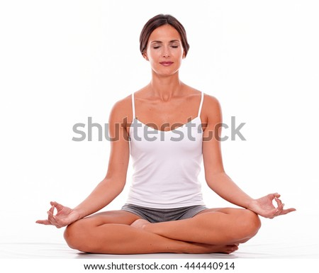 Young brunette woman sitting with her legs crossed while meditating with closed eyes and wearing a white tank top and gray shorts isolated