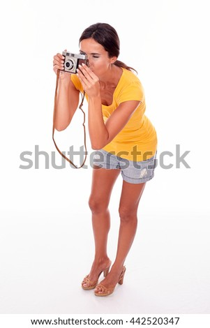 Young brunette woman taking a photograph while focusing away and wearing a yellow t-shirt and short jeans on white background
