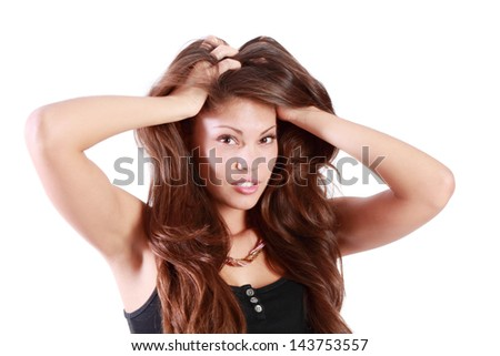 Young brunette woman touches her hair and looks at camera isolated on white background.