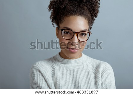 Young brunette woman wearing glasses and a sweater, posing over gray background