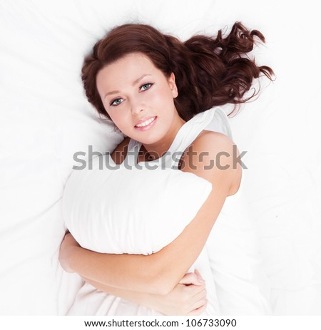 young brunette woman  with a pillow in bed at home, top view - stock photo