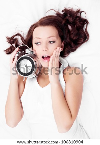 young brunette woman with alarm clock  in bed at home, top view - stock photo