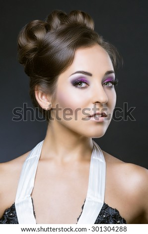 young brunette woman with beautiful makeup and hair, against dark studio backround - stock photo