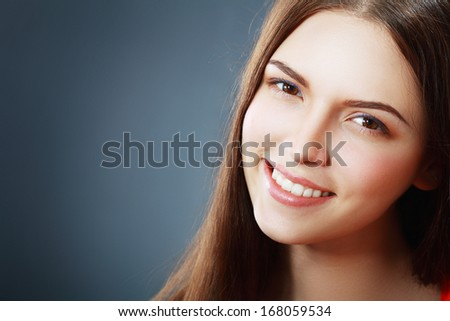 Young brunette woman with beautiful smile over dark background close up - stock photo