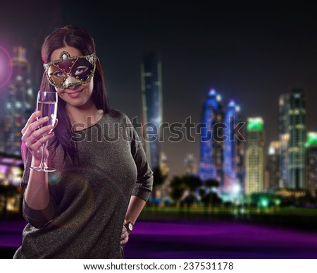Young brunette woman with champagne glass in city at night. Celebration theme. - stock photo
