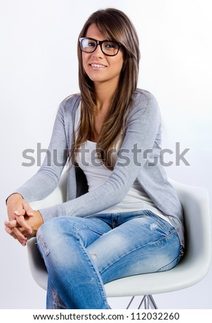 Young brunette woman with glasses sitting on a chair