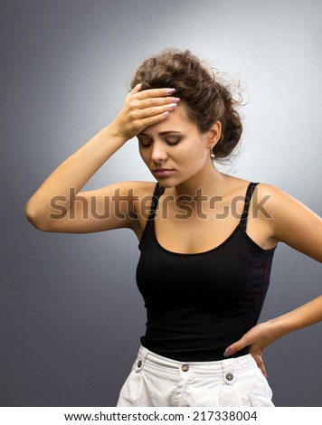 Young brunette woman with headache holding her head, isolated on grey light background - stock photo
