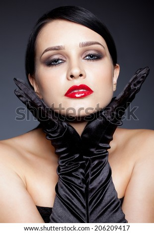 Young brunette woman with long black gloves posing on gray background