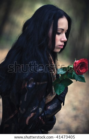 Young brunette woman with red rose portrait. Dark colors. - stock photo