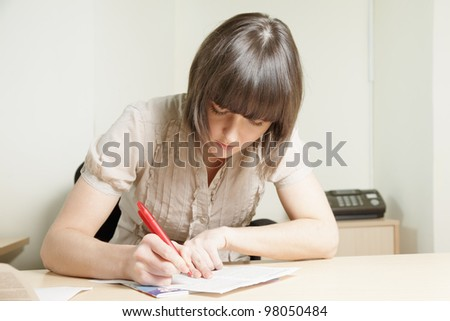 Young brunette woman writing on paper sheet at office desk