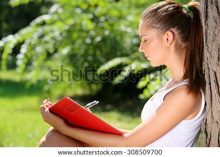 young brunette woman writing to notepad, leaning against a tree - stock photo