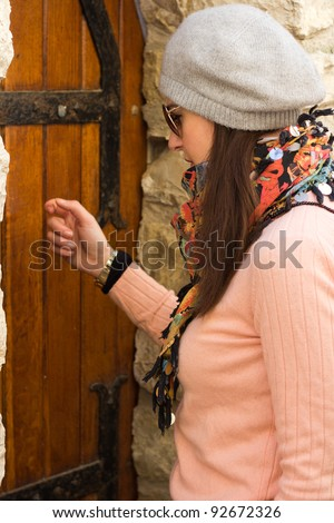 Young Brunette Women With Sunglasses Knocking On An Old Wooden Door Taken From Close-Up
