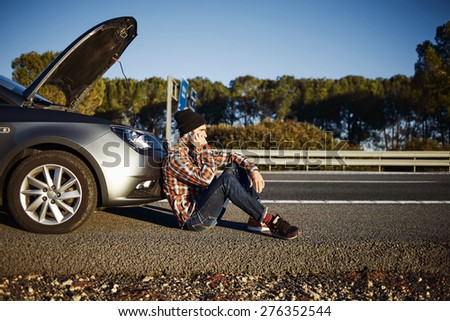 Young brutal man sits near car talking on cell phone because his auto broken down. Caucasian male on a beautiful bright sunny summer day trying to call friend that they help repair car.  - stock photo