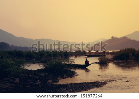 young buddhist monk on fisher boat at sunset on Mekhong in Luang Prabang - Laos - stock photo