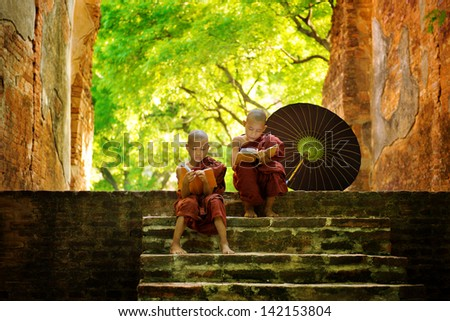 Young Buddhist monk reading outdoors, sitting outside monastery, Myanmar. - stock photo
