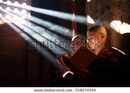 Young Buddhist novice monk reading in monastery. Beautiful natural sunlight from window. Buddhist teaching, Myanmar. - stock photo