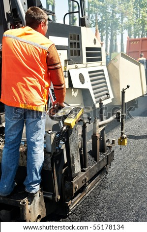 Young builder and Asphalt paver machine during Road street repairing works - stock photo