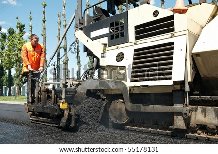 Young builder and Asphalt spreader during Road street repairing works