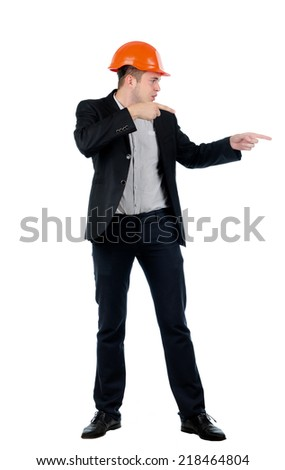 Young builder, architect or engineer in a suit and hardhat standing pointing with both hands to the right of the frame and blank copyspace - stock photo
