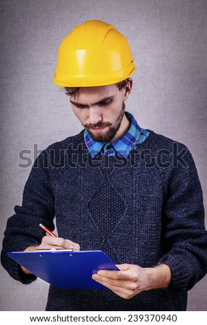 Young builder in helmet thought about project - stock photo