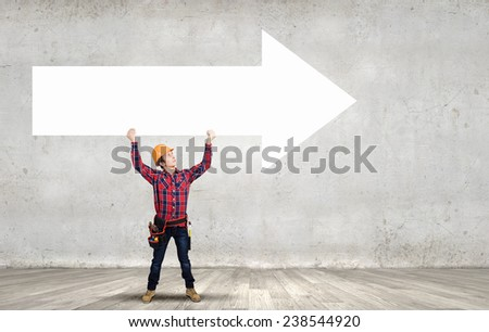 Young builder man in hardhat holding white blank arrow - stock photo