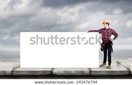 Young builder man in hardhat holding white blank banner - stock photo