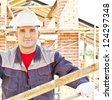 Young builder on a background of metal roof trusses - stock photo