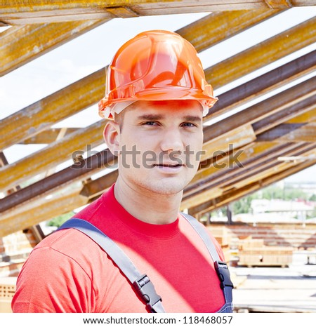 Young builder on a background of metal roof trusses