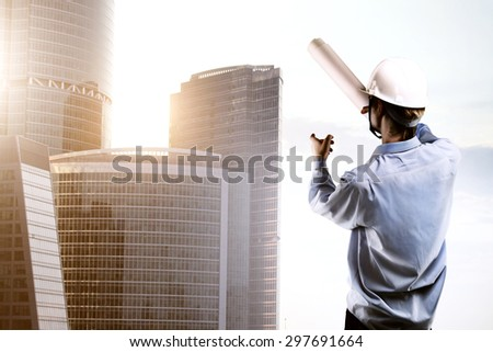 young builder standing and pointing at skyscraper - stock photo